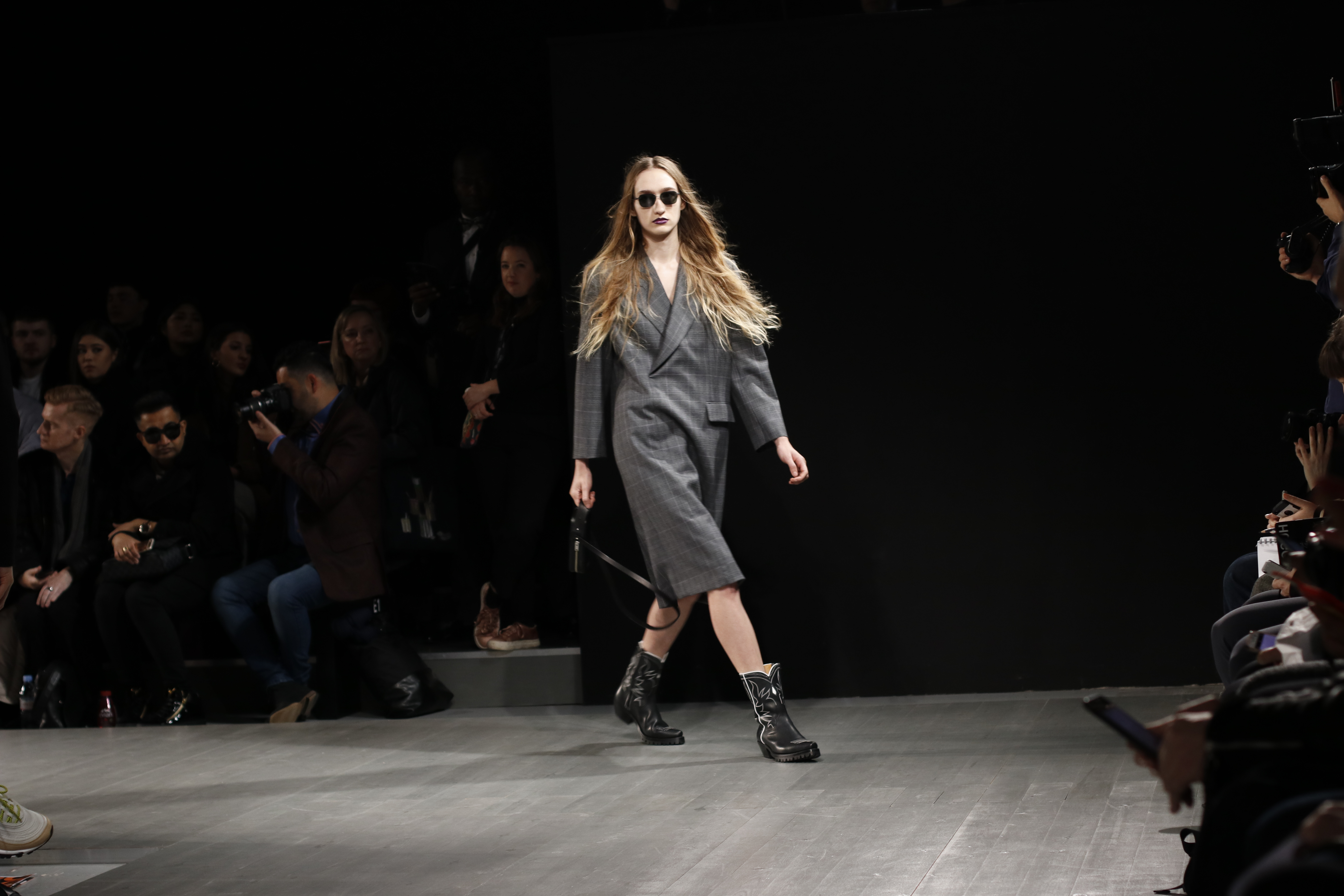 model in grey long coat walking on catwalk