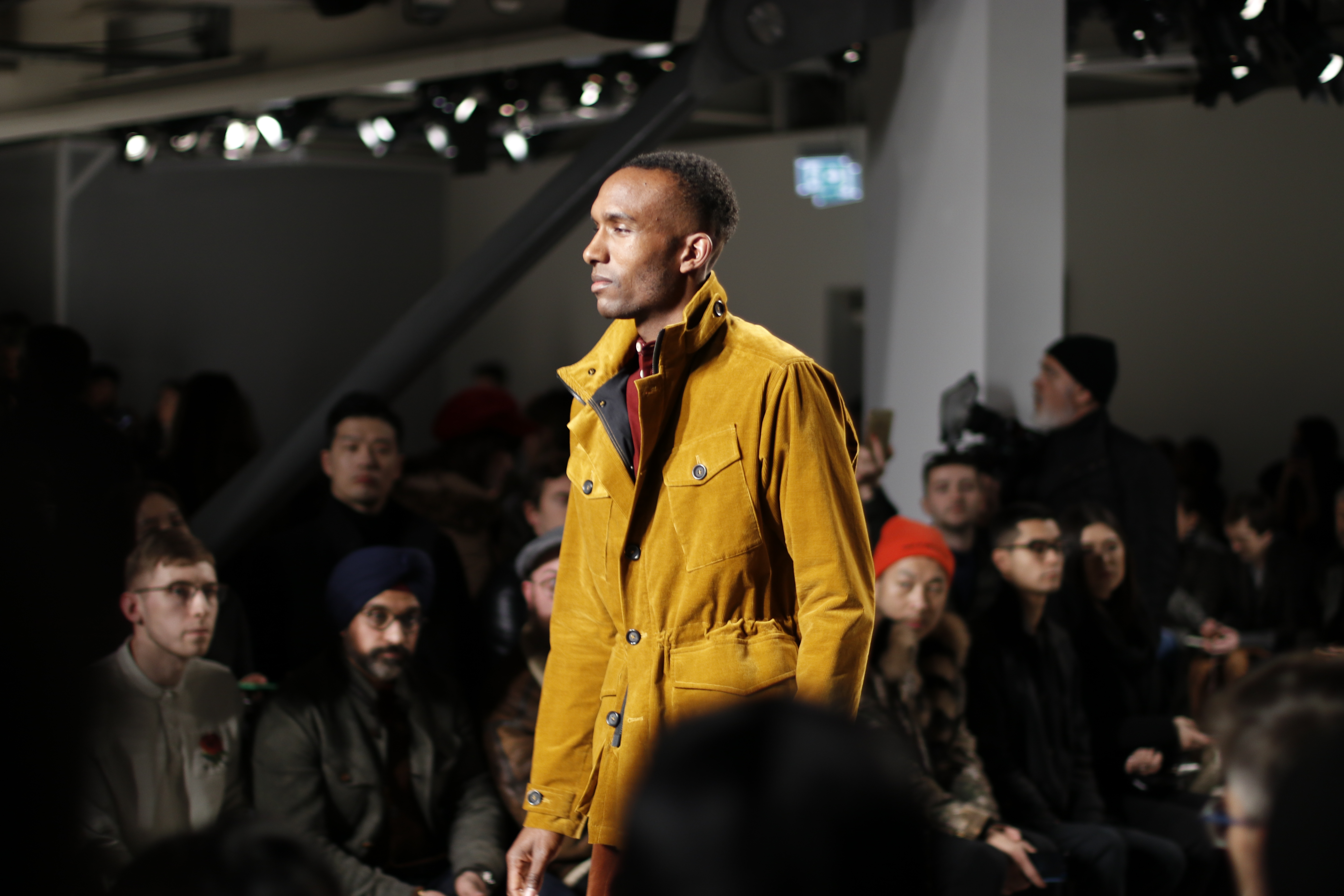 male model wearing mustard jacket on catwalk